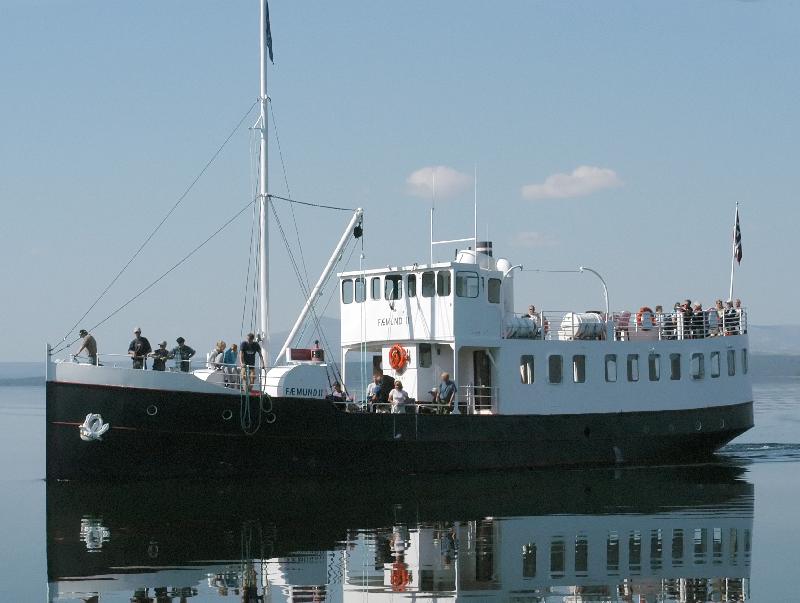 Bilde viser båten Fæmund II på sjøen en finværsdag