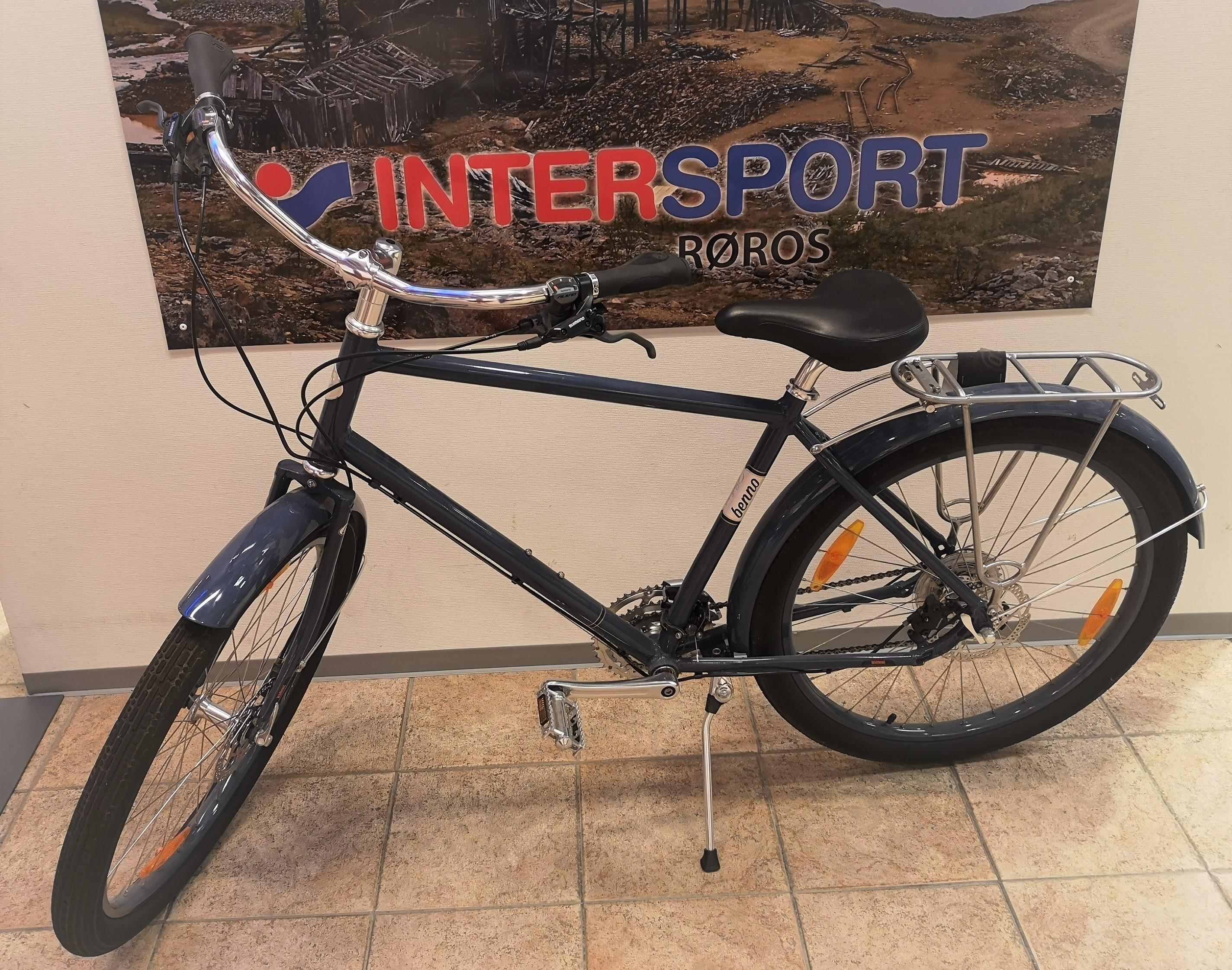 Bilde av en blå sykkel. På veggen bak henger en plakat med logoen til Intersport.