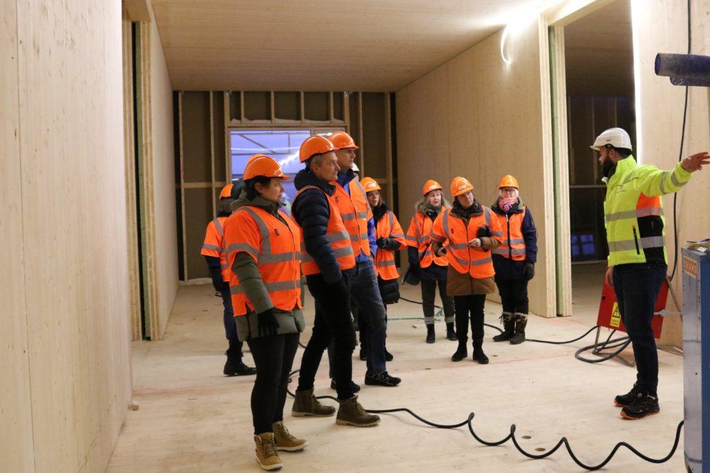Bilde fra innsiden på byggeplassen med prosjektleder som informerer og gruppen lytter