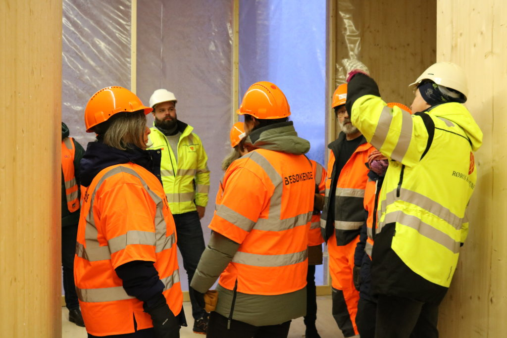Bilde fra innsiden av bygget, mens deltagerne på befaring og prosjektlederen står foran ett av de store vinduene i 2. etasje