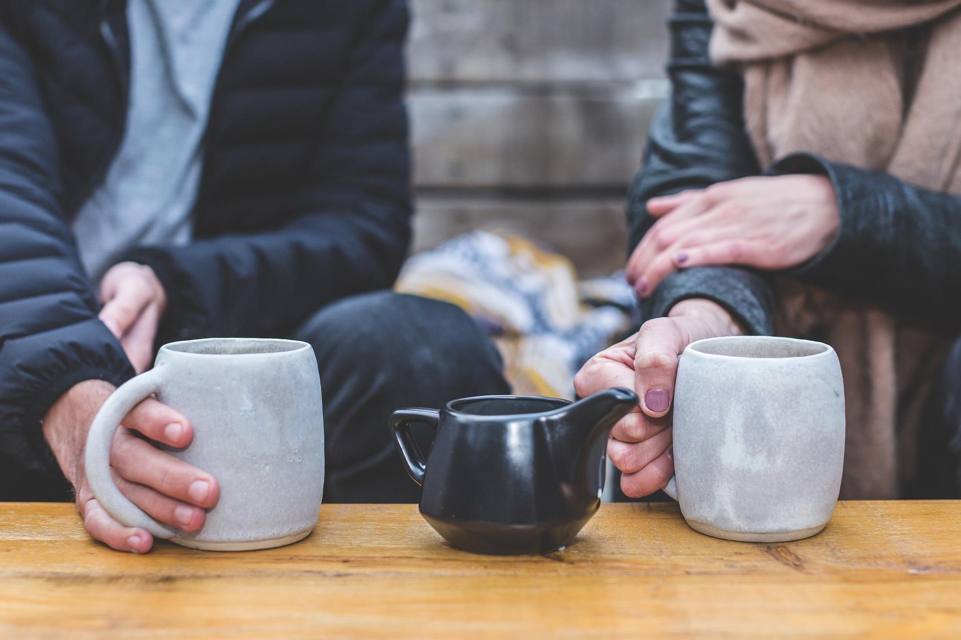 to mennesker som sitter ute og drikker kaffe sammen