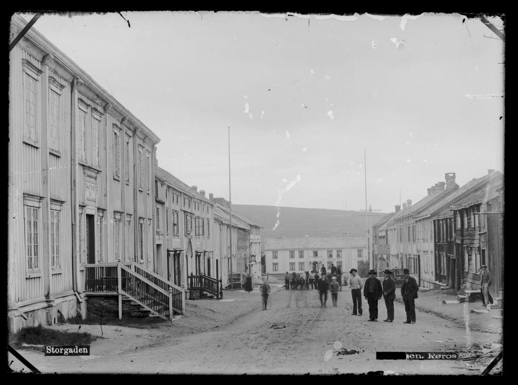 Historisk sort-hvitt-bilde som viser rådhusgården rundt 1890, med en gruppe mennesker som står i gata til høyre for gården.