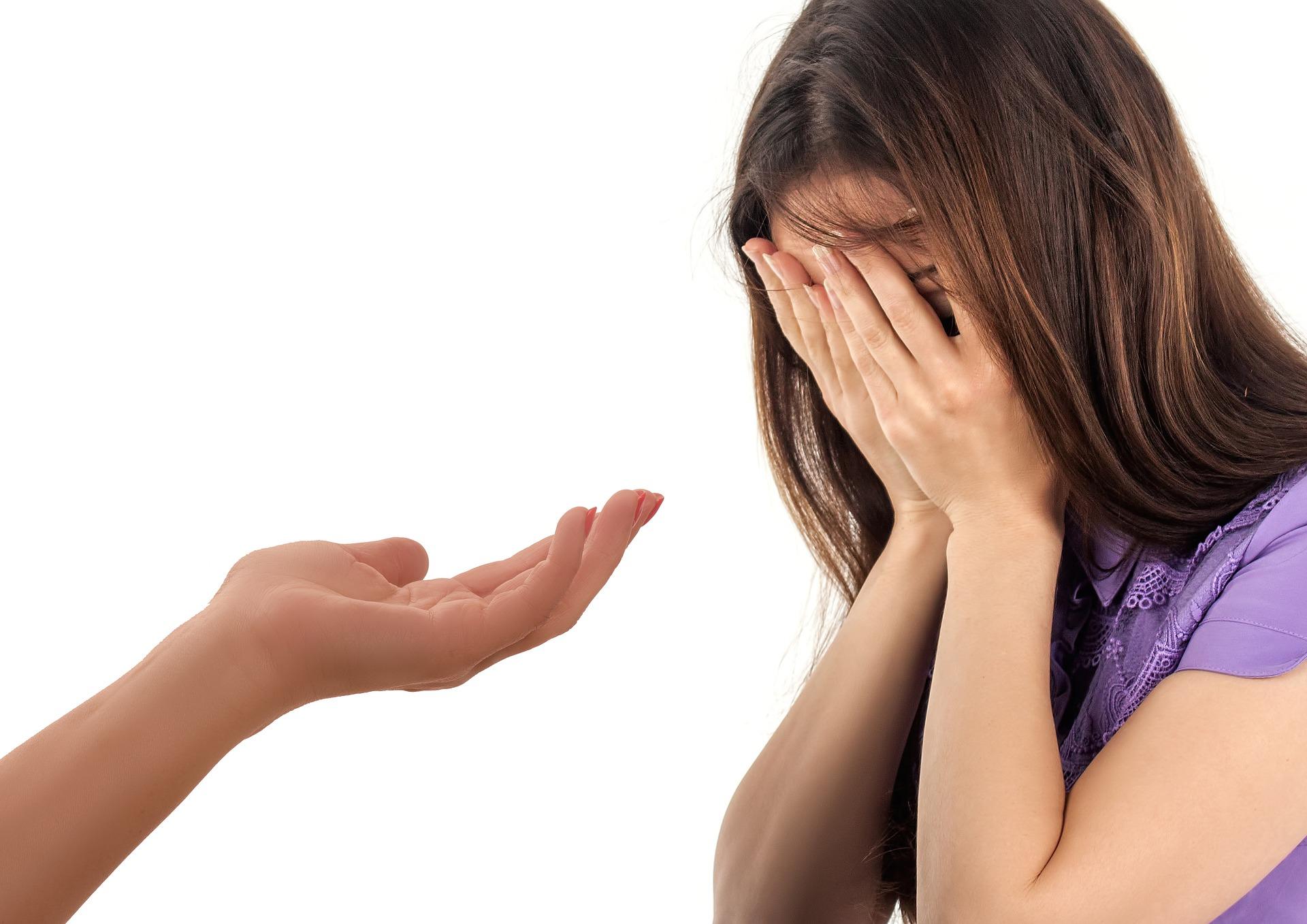 Bilde av kvinne som holder hendene forran ansiktet og hånden til en annen person som rekkes ut forran henne