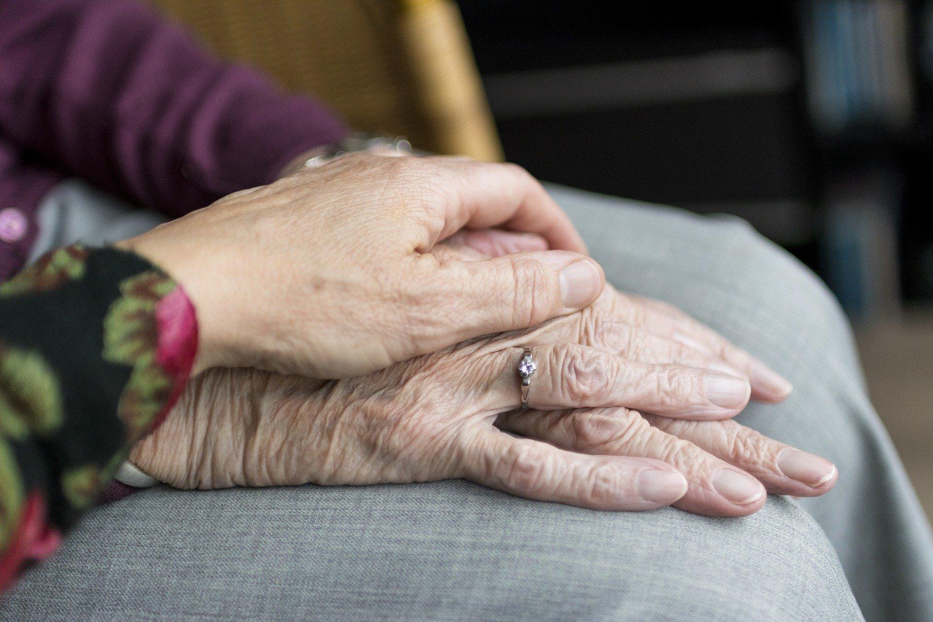bilde av hendene til en eldre person som ligger på kneet. En annen person har lagt hånden sin over den eldres hender.