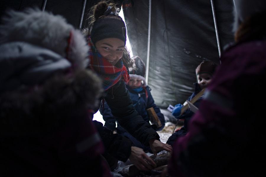 En kvinnelig barnehageansatt og noen barn som sitter å hygger seg i en lavvo. Den ansatte smiler, og hjelper barna med å få i stand et bål. Det siver litt lys inn i lavvoen.
