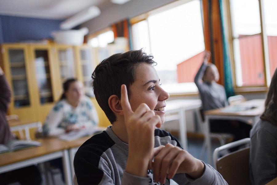 Bilde er tatt i en skoletime, og viser en elev som smiler mens han rekker opp hånda. I bakgrunnen ser man konturene av flere elever.