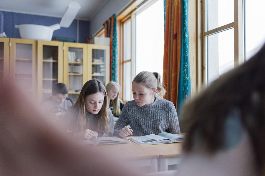 Bilde er tatt i en skoletime, og viser to jenter som jobber med skolearbeid. Jentene ser konsentrerte i ei bok. Både foran og bak dem i klasserommet ser man flere elever som sitter å jobber.