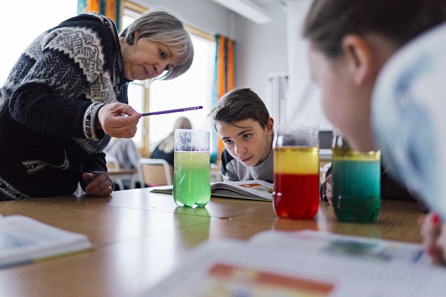 Bilde viser en kvinnelig lærer som utfører et naturfagforsøk sammen med to elever som sitter ved en skolepult der det står tre glass som inneholder farget væske. Elevene virker nysgjerrige, og ser på det ene glasset.