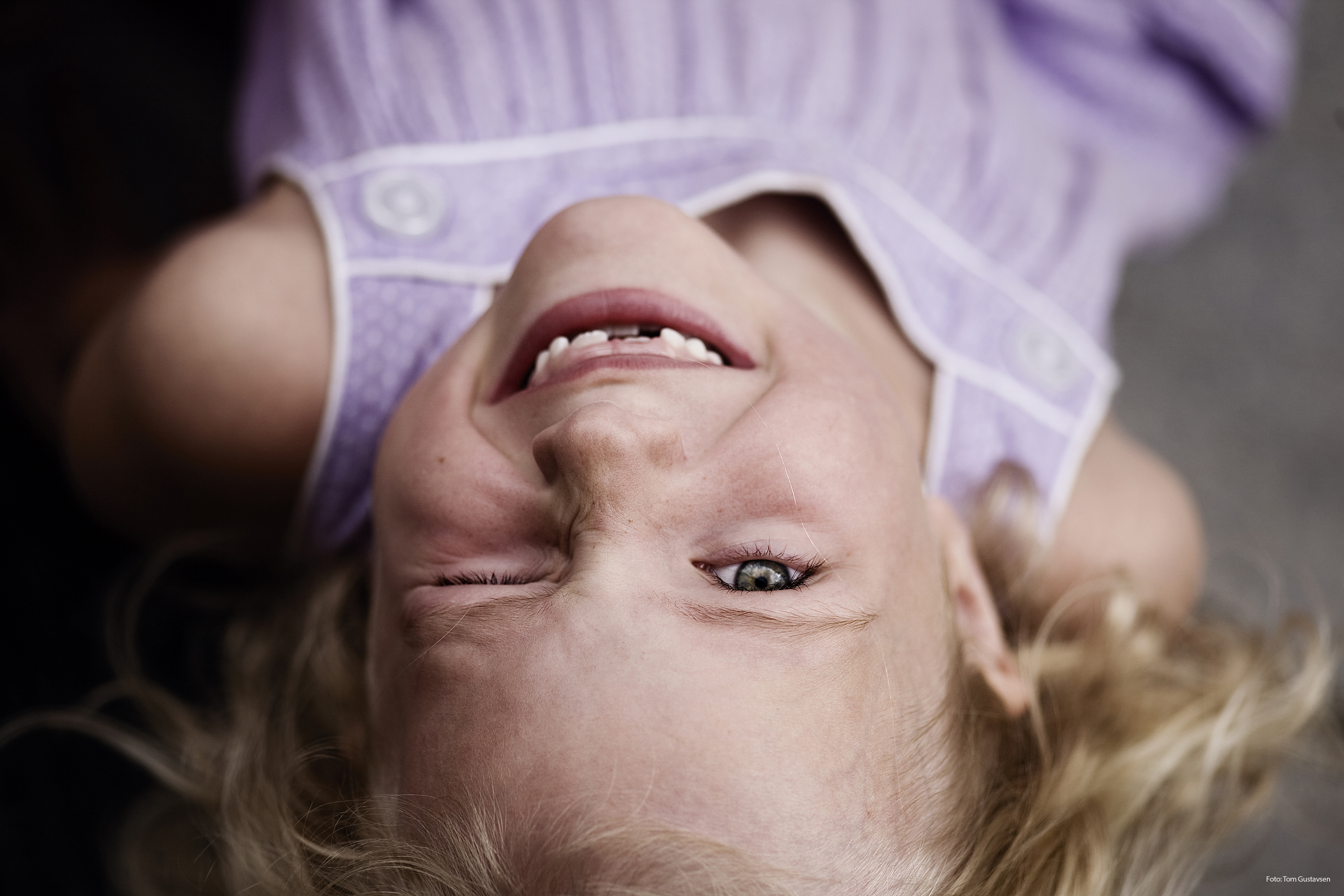 Ei barnehagejente i lilla kjole ser i kameraet og smiler med et øye lukket. og har et øye igjen.