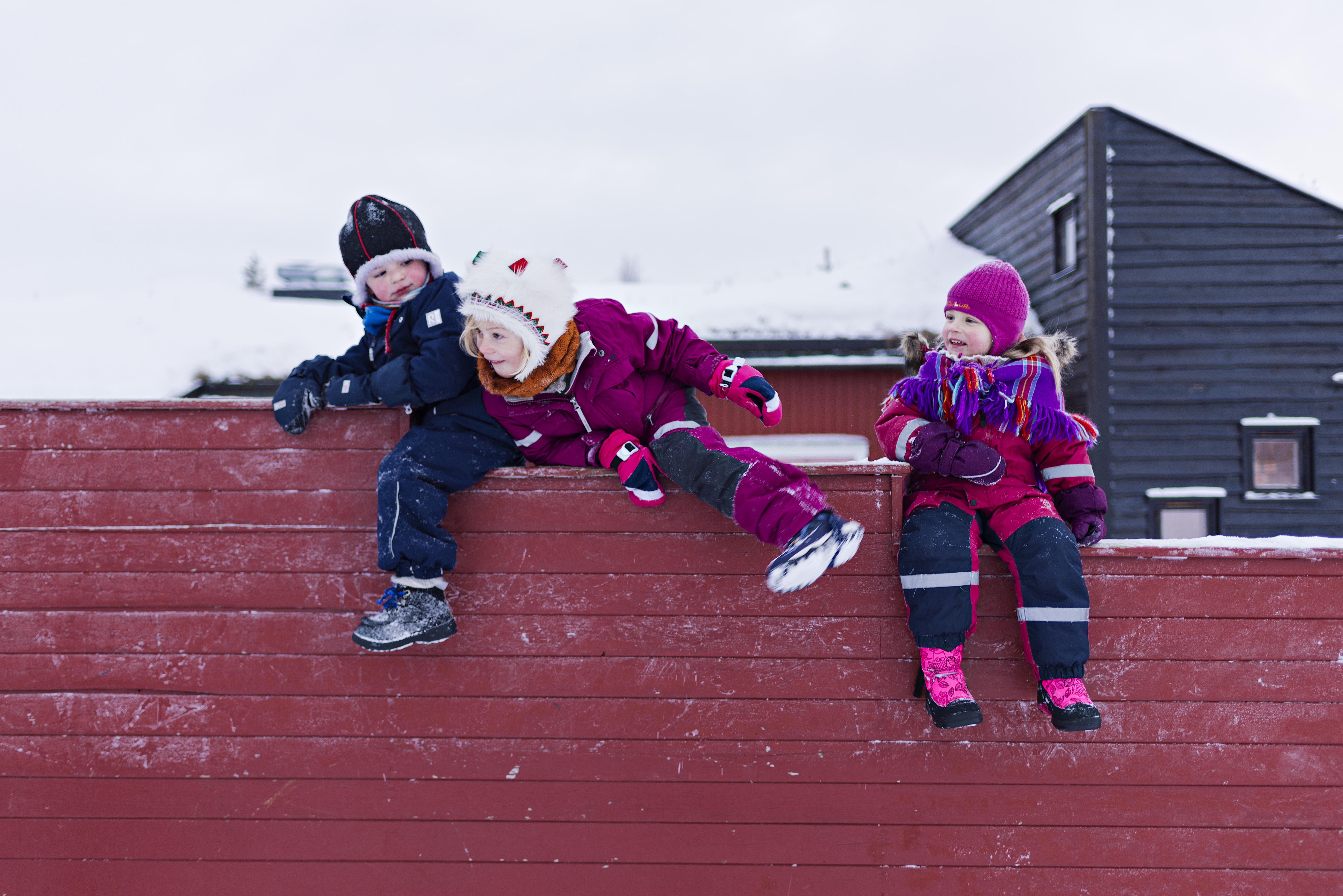 Vinterbilde med tre barnehagebarn i vinterdresser som sitter på et rødt gjerde.