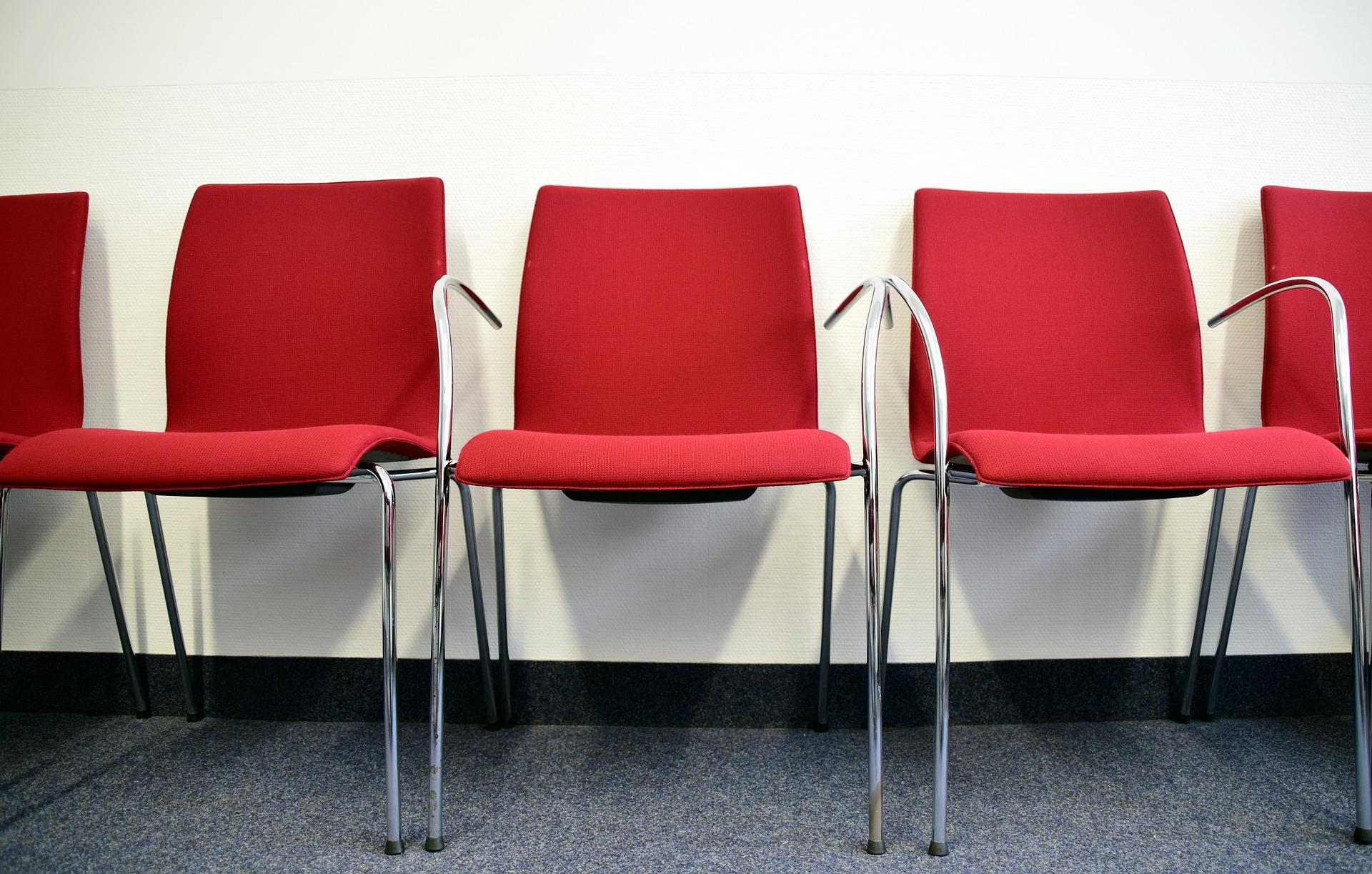 bilde av en rekke med tre røde stoler langs veggen i et rom