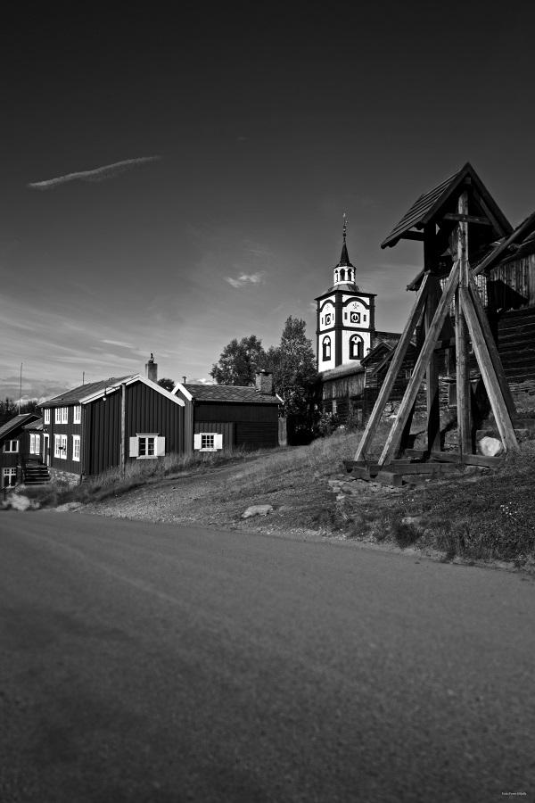 Bilde av Hyttklokka med kirketårnet i bakgrunnen. Bilde er tatt på våren/sommeren. Det er et svart/hvittbilde.
