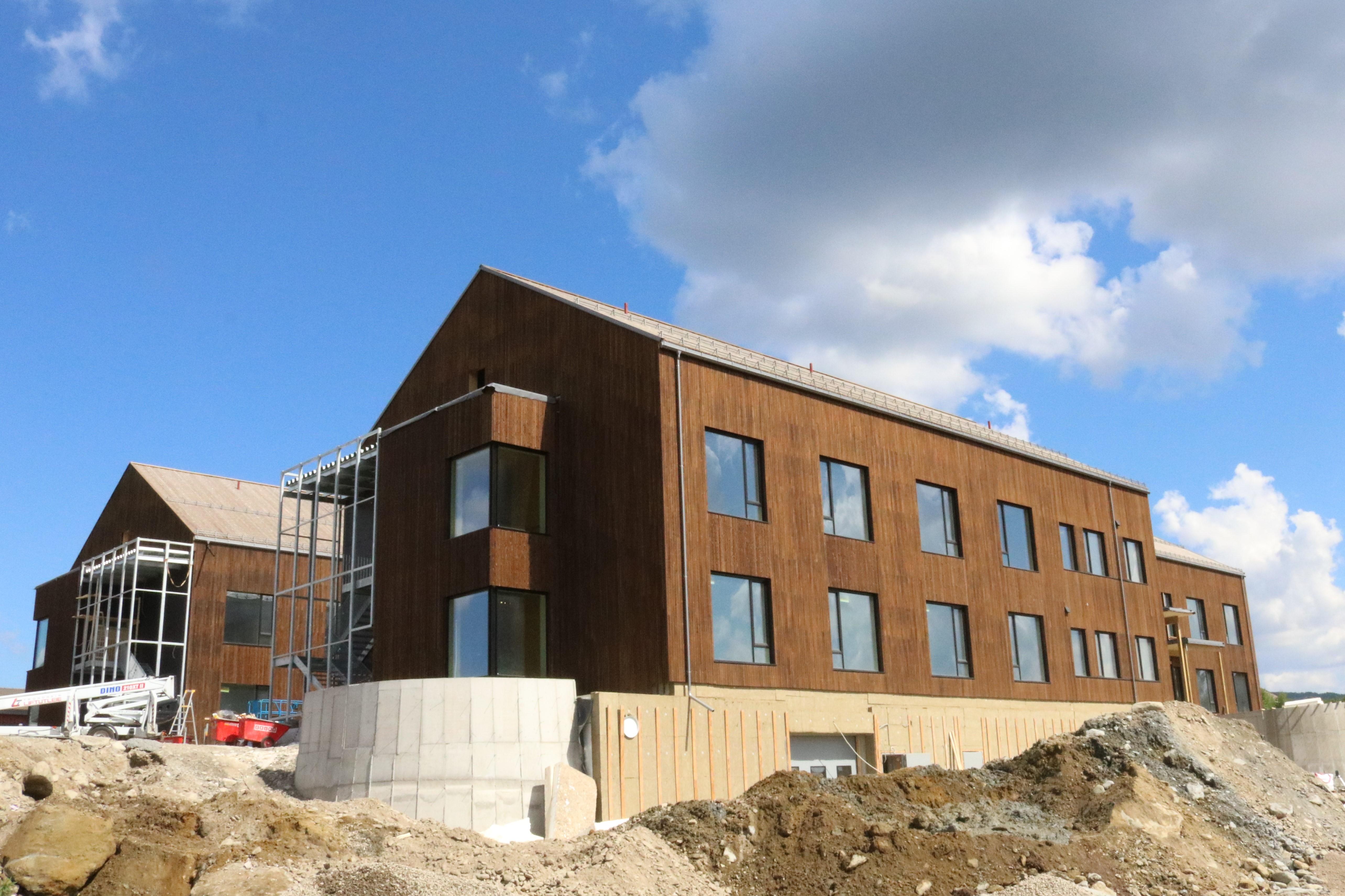 Bilde tatt ute av det nye sykehjemsbygget, om sommeren med blå himmel bak.