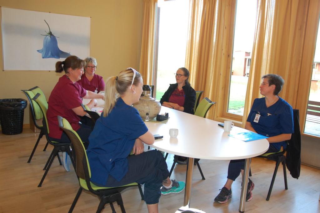 Fem damer i hjemmetjenesten sitter rundt et møtebord, med store vinduer i bakgrunnen