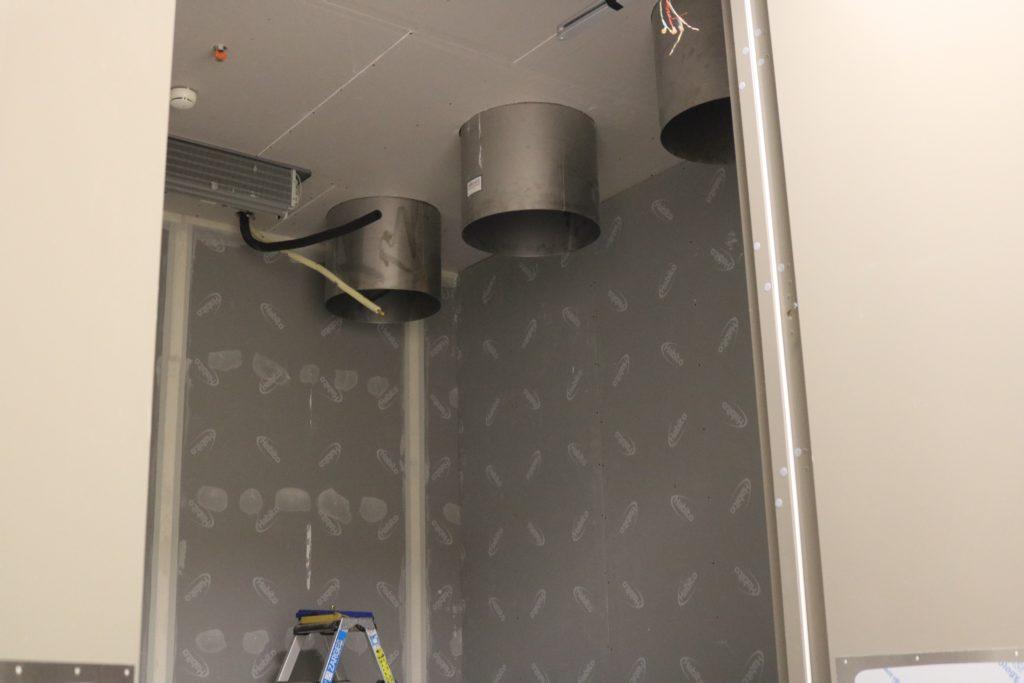 Bilde inn i kjellerommet som viser avfallssjakten som kommer ut oppe i taket