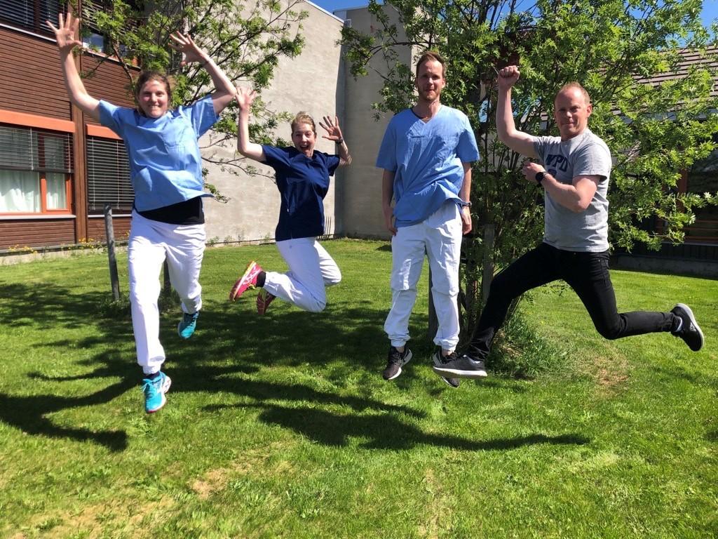 Bilde av to damer og to menn som hopper opp ute på en grønn gressplen, foran et tre