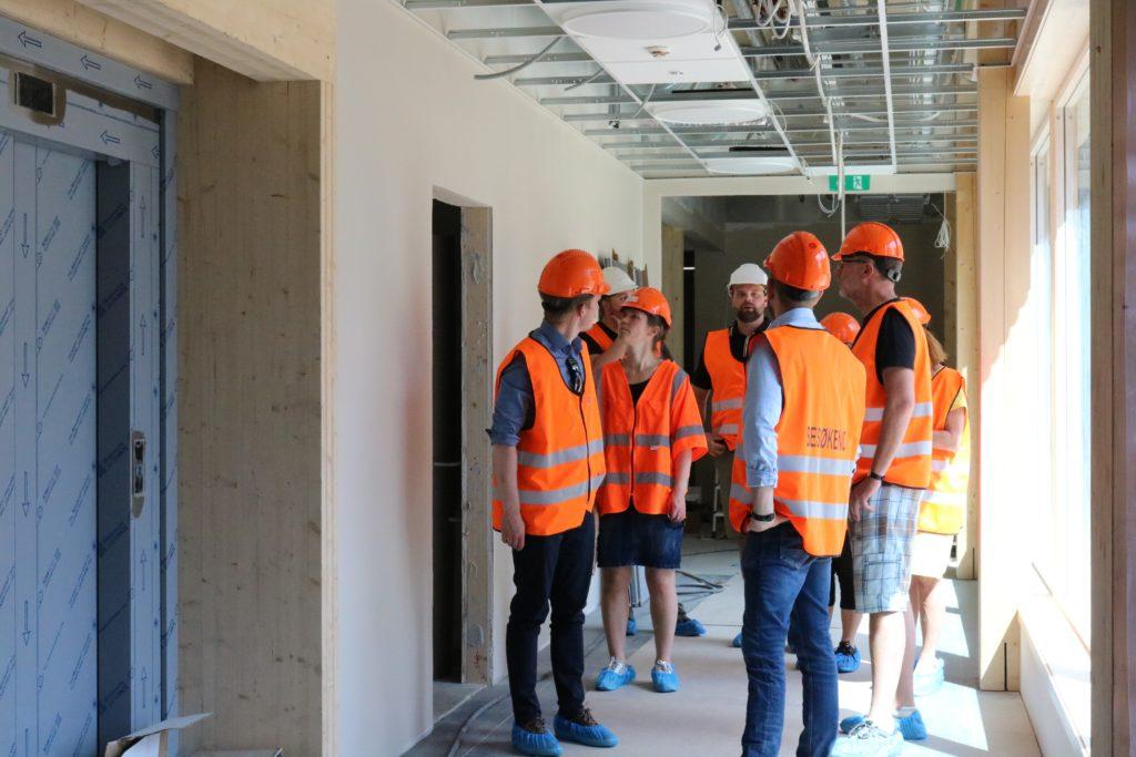 Bilde av fem personer med vest og vernehjelm i gangen på byggeplassen