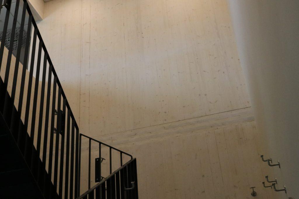 Bilde fra trappeoppgangen som viser deler av det sorte rekkverket og den høye veggen i massivtre som går oppover i hele trappeoppgangen