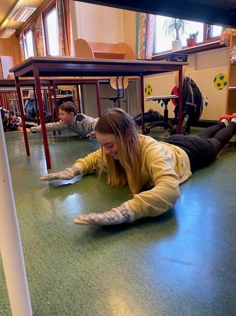 en gutt og en jente ligger magen på gulvet i klasserommet og løfter armer og ben