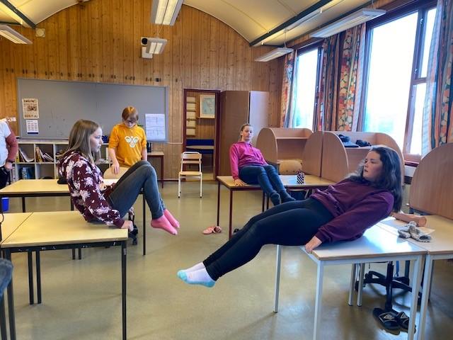 tre jenter sitter på skrivepulten sin i klasserommet. De trekker knærne mot magen. En gutt står ved pulten sin.