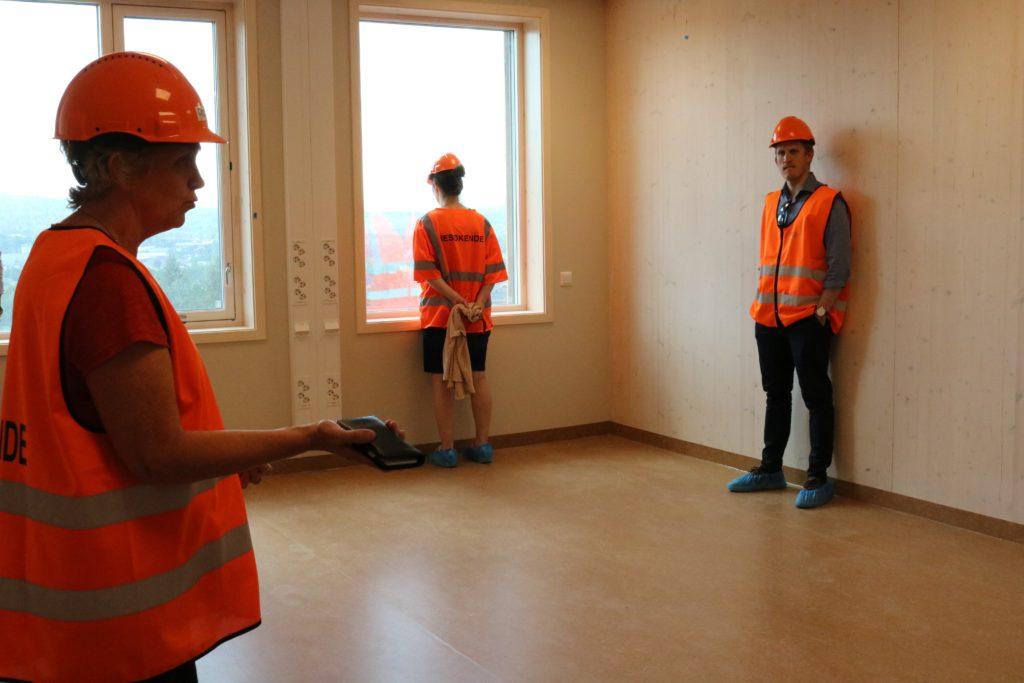 Tre personer på befaring står ved hver sin vegg inne på et av de nye pasientrommene, uten møbler