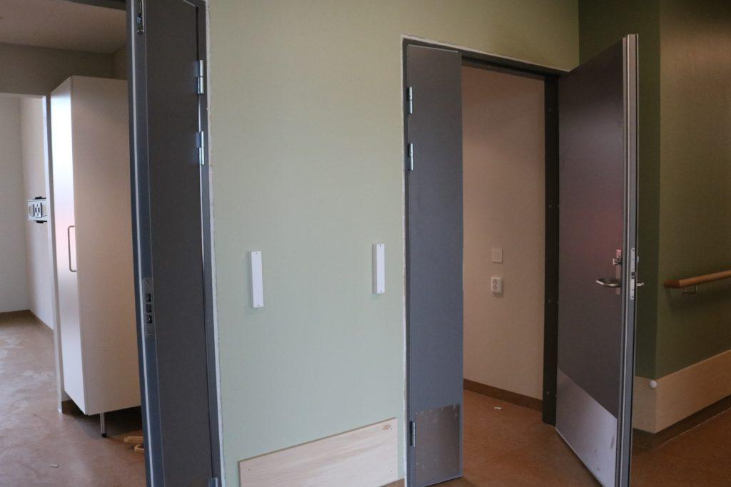 bilde fra den grønne gangen som viser dørene inn til to pasientrom, på veggen ved hver dør ser vi de hvite posisjonsvardene