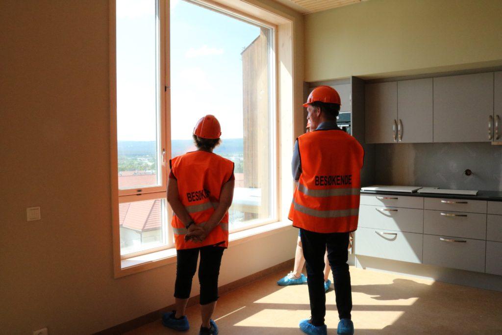 to personer står forran vinduet og kikker ut, på felleskjøkkenet
