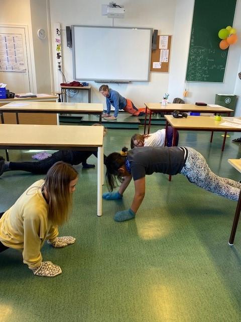 Tre jenter, en gutt og en dame står på hender og kne på gulvet i klasserommet. De har votter på hendene og gjøre en øvelse for å styrke kjernemuskulaturen.