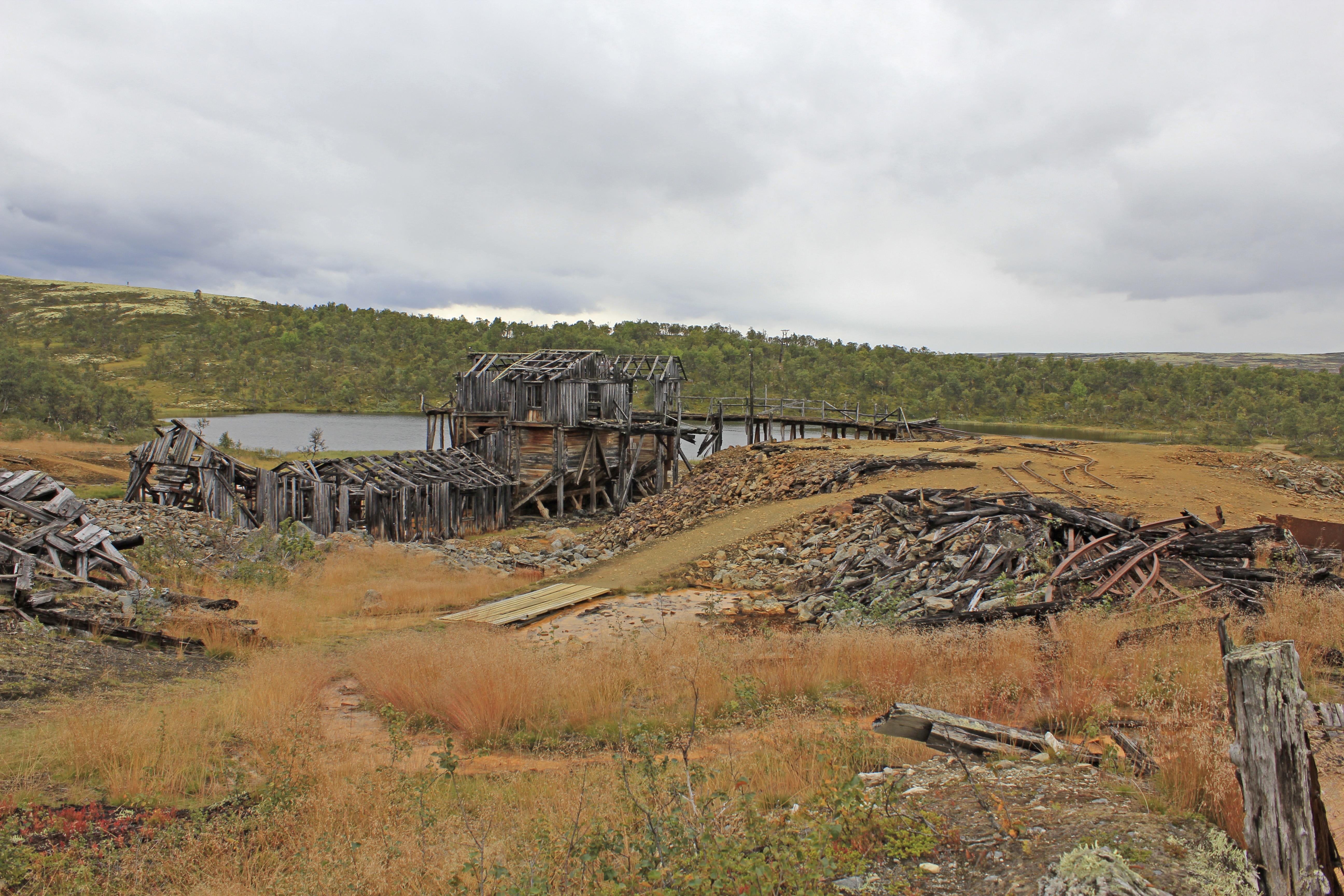 Landskapsbilde med gammel gruvebygning, bakken i forgrunnen er rød etter gruvedrift, med små slagghauger og gammelt materiale og metall etter gruvedrifta. Bak bygningen er en liten innsjø forran en ås med grønne trær, over er himmelen dekket av skyer