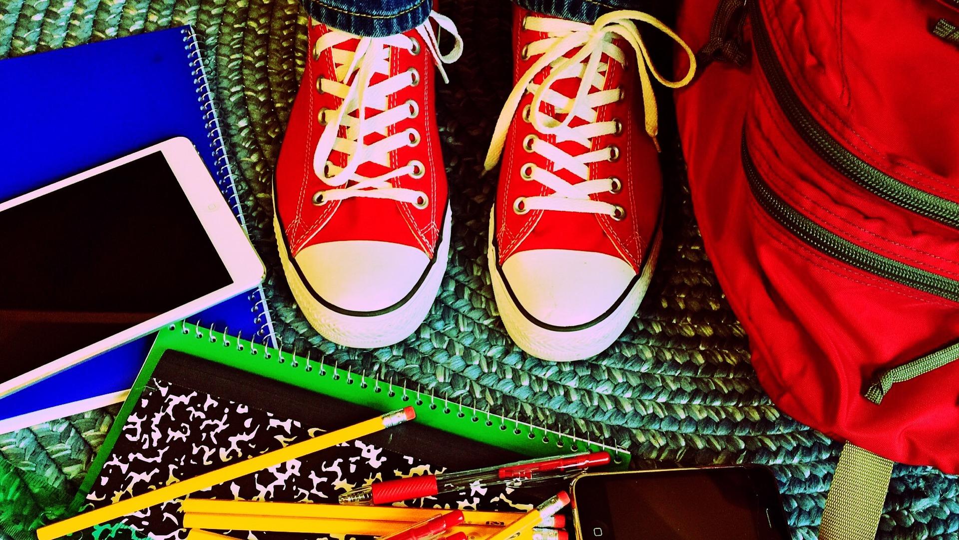 Illustrasjonsfoto som viser føttene på på en ungdom som har på seg røde sneakers-sko i midten, rundt føttene på gulvet ligger ett par spiralblokker, en ipad og en iphone, blyanter og linjal og til høyre står en rød skolesekk.