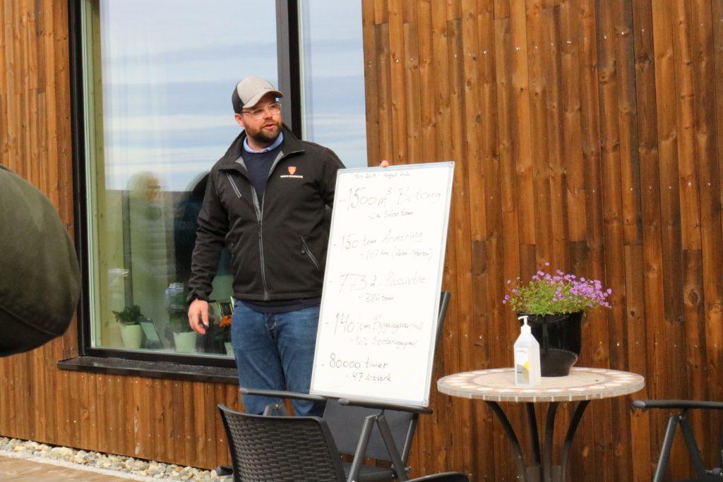 Prosjektleder Mads Tamnes står forran fasaden på det nye bygget, han har en tavle med fun facts som han presenterer