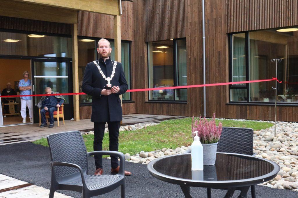 Ordfører Isak Veierud Busch med ordførerkjede, står foran den røde snoren, det nye bygget i bakgrunnen