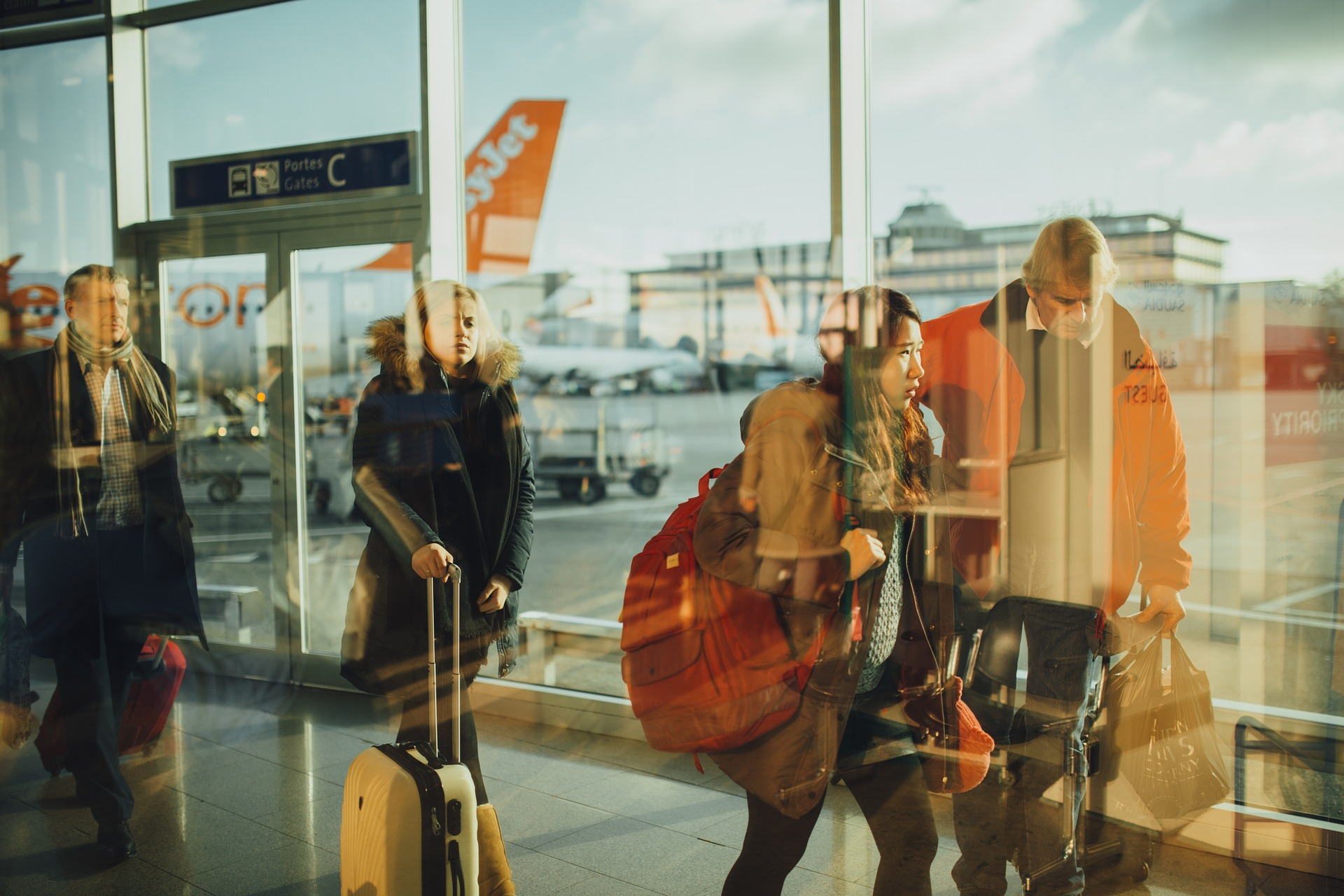 Bilde av en glassvegg på en stasjon eller flyplass som reflekterer tre personer med koffert