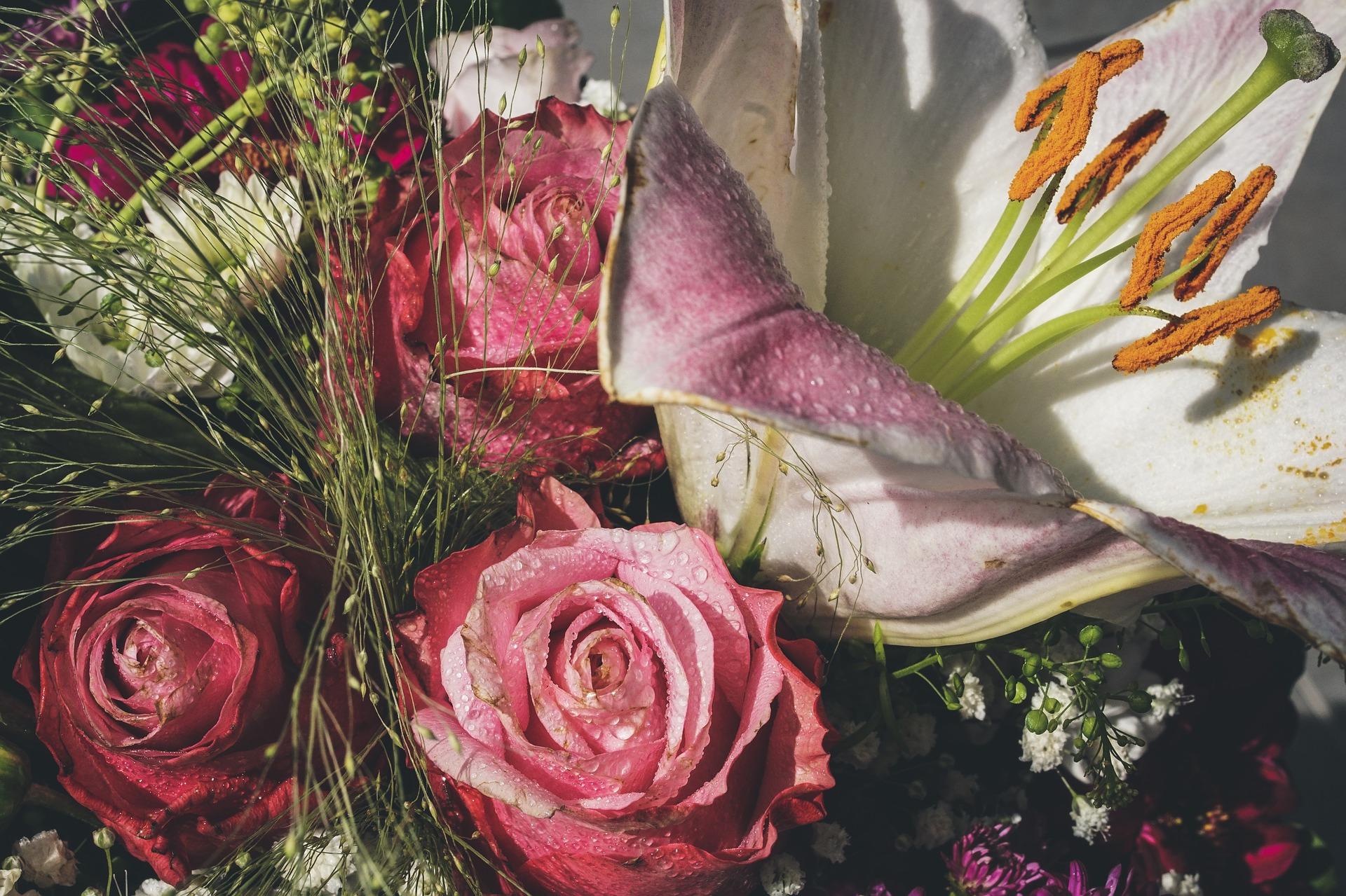 Foto av en bukett med rosa roser og hvite liljer