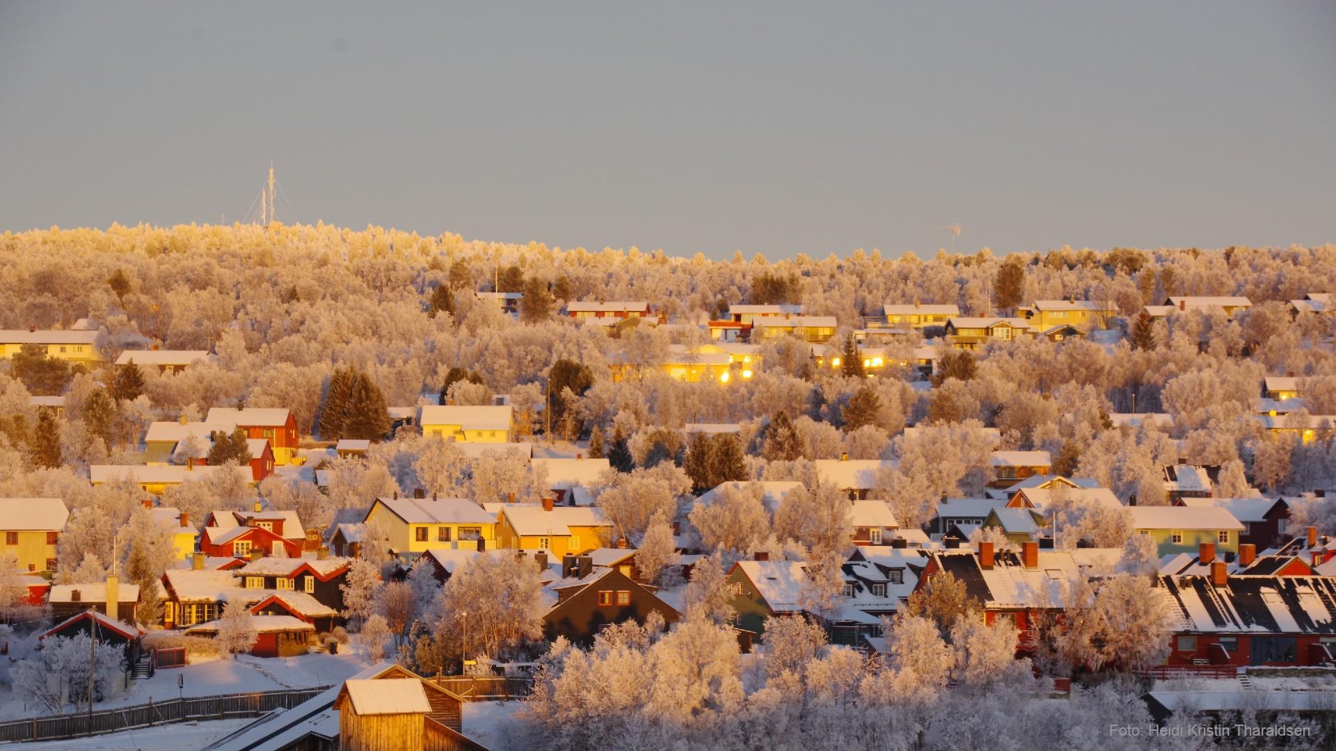 Bilde av en ås med mange bolighus, mot en blå himmel, en kald vintermorgen