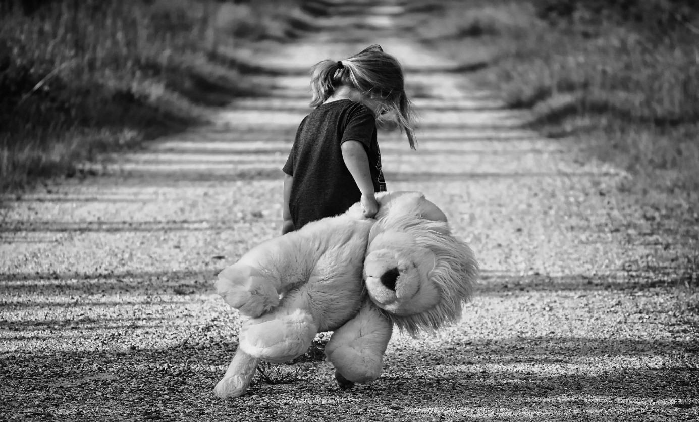 Bilde er svarthvitt, og viser ei jente som står på en vei med en stor kosebamse i hånda.