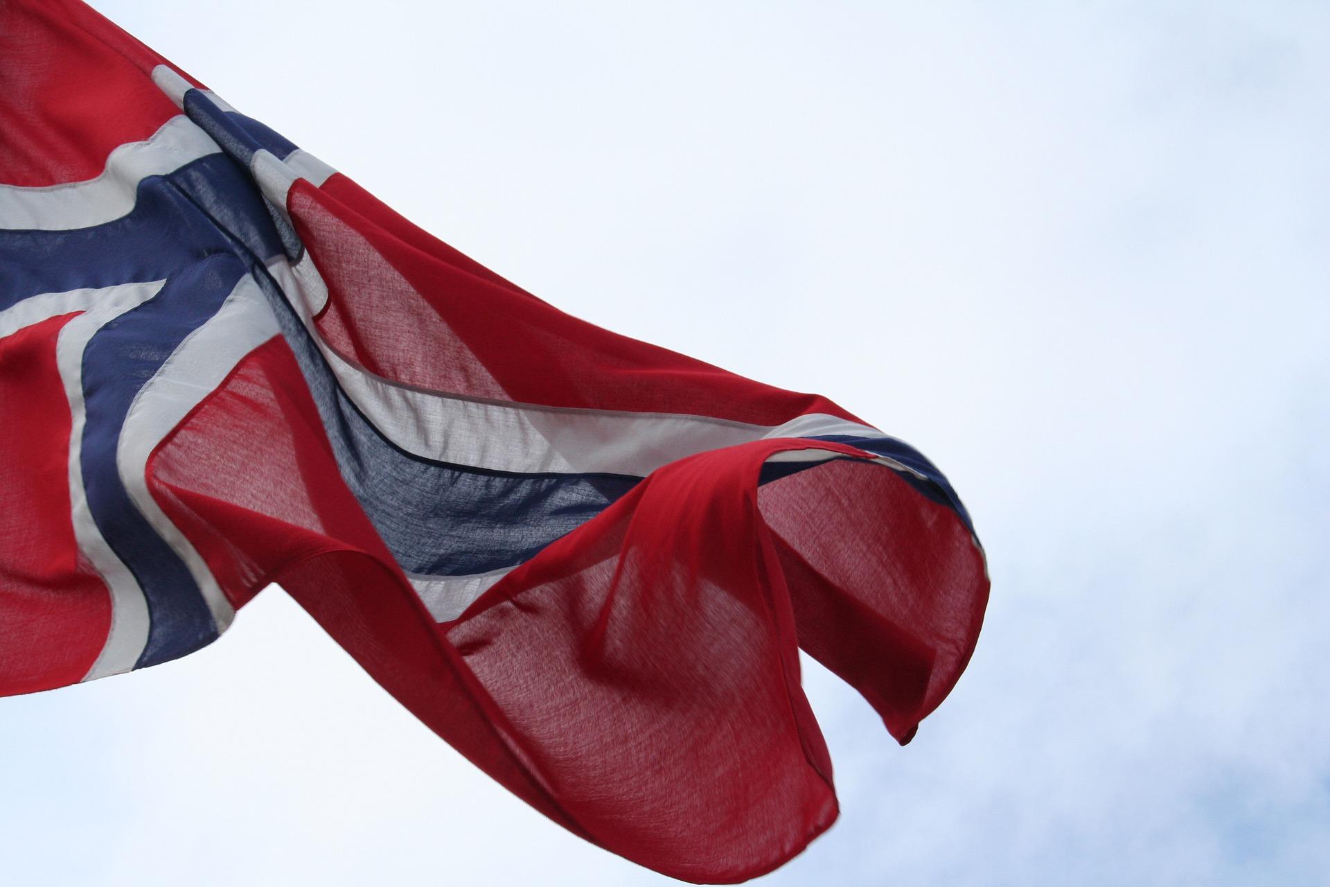 bilde at det norske flagget som vaier i vinden mot en blå himmel