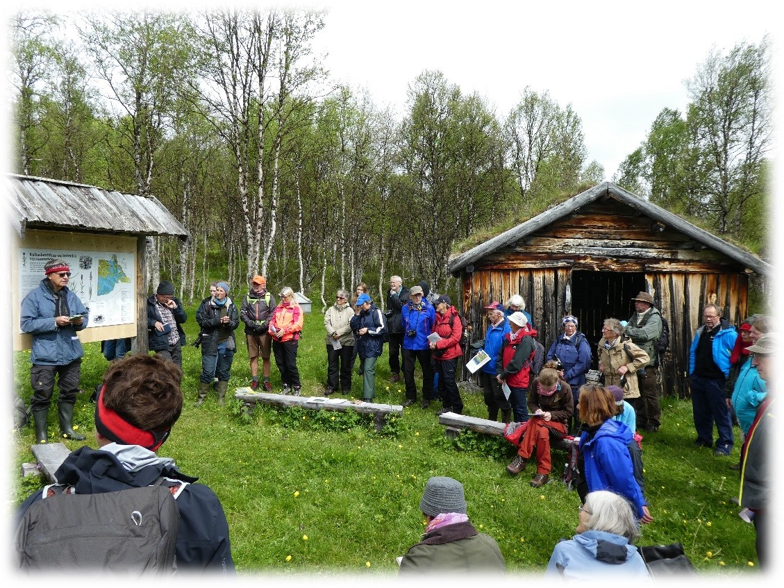 En gruppe folk som sitter i naturskjønne omgivelser