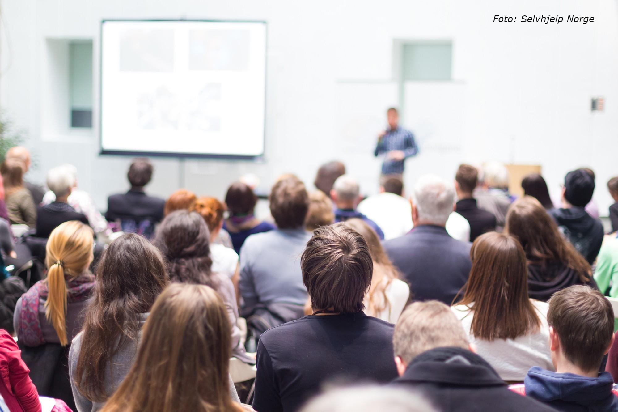Bilde av mennesker som sitter og ser på en presentasjon